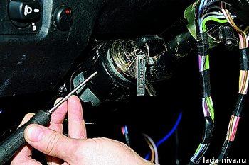 шлицевой отверткой с узким лезвием утапливаем фиксатор выключателя зажигания через отверстие в боковой стенке...